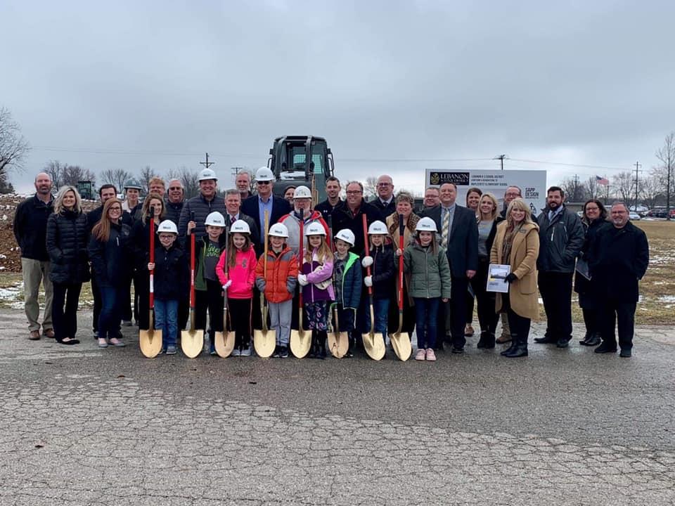 Adults and kids in hardhats holding golden shovels for winter groundbreaking Maplecrest Elementary School